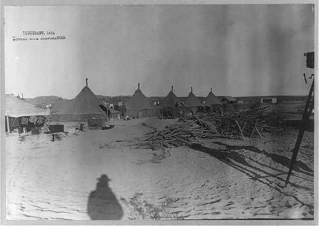 [U.S. Army tent camp in Mexico, 1914: row of tents; movie camera at far right]