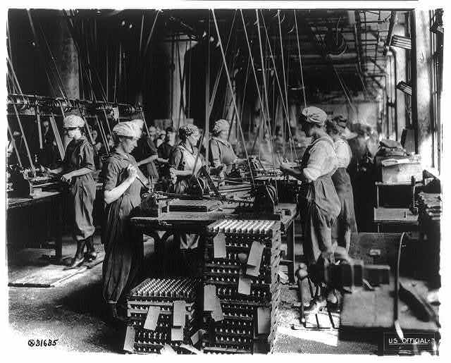 Women working in ordnance plants in World War I: spanner slotting fuse on head end of fuse bodies at Gray & Davis Co., Cambridge, Mass.