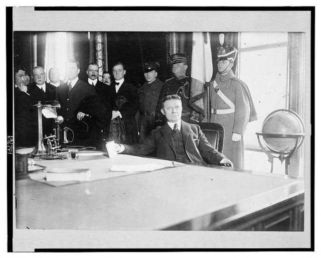 [Charles Seymour Whitman, half-length portrait seated at desk, with dignitaries behind him, on the occassion of his inauguration as governor of New York state, Albany, 1915]