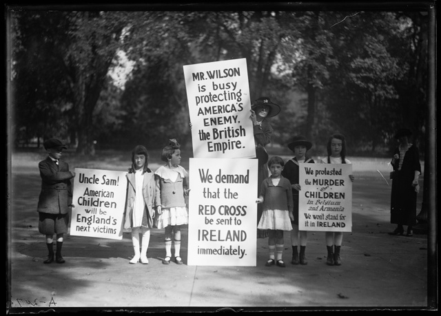 """[Children protesters with signs: """"Mr. Wilson is busy protecting America's Enemy. The British Empire,"""" etc.]"""