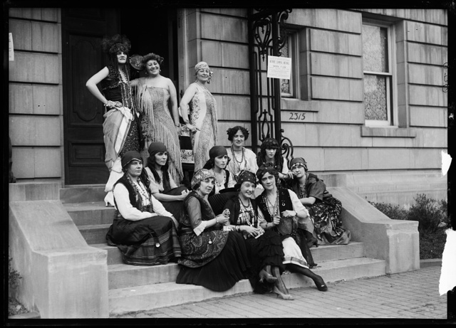 "[Group in costume on steps; sign: ""League of American Pen Women, Authors' Carnival and Ball ... Book Fair ... Massachusetts Ave. [Washington, D.C.]"