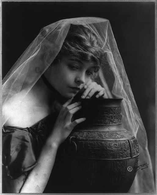 [Lillian Gish, head-and-shoulders portrait, facing right, leaning on large pottery vase]