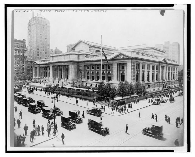 [New York Public Library as seen from building across intersection of E. 42nd Street and Fifth Ave., showing front and east facades, as well as automobile and pedestrian traffic]