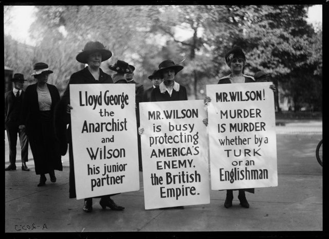 "[Protesters with signs: ""Lloyd George the Anarchist and Wilson his junior partner,"" ""Mr. Wilson is busy protecting America's enemy. The British Empire,"" and ""Mr Wilson! Murder is Murder whether by a Turk or an Englishman"""