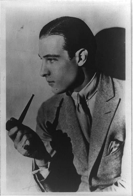 [Rudolph Valentino, half-length portrait, facing left, holding pipe]
