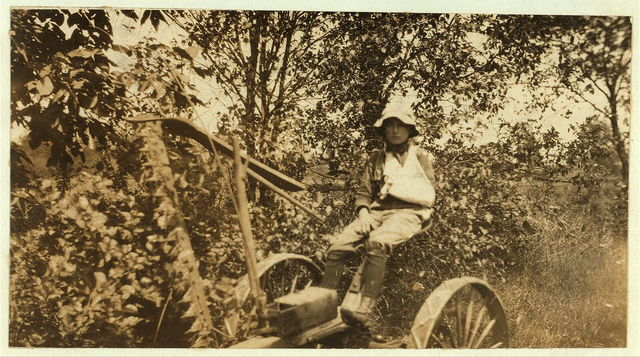 Rural Accident. Twelve-year old Clinton Stewart and his mowing machine which cut off his hand. See Hine Report, August 1915.