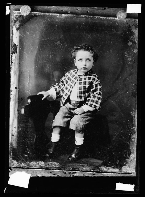 [Seated boy in checkered jacket]