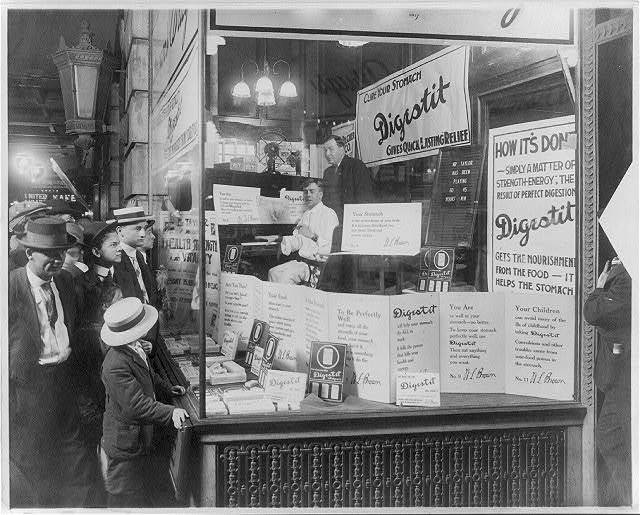 "[Shoppers looking at window display of Brown's Drug Store, advertising ""Digestit,"" a stomach relief patent medicine; product is being endorsed by a pianist, ""Mr. Thomas,"" who has been playing in the store window non-stop for 60 hours and 45 minutes; Mr. W.L. Brown in standing behind Mr. Thomas.]"