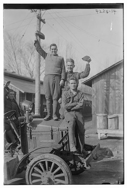 [Unidentified men posing on automobile]