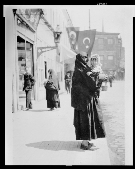 [Woman holding a baby on a street in Istanbul]