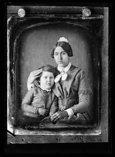 [Woman in coiffed hair with comb, and boy, possibly her son]