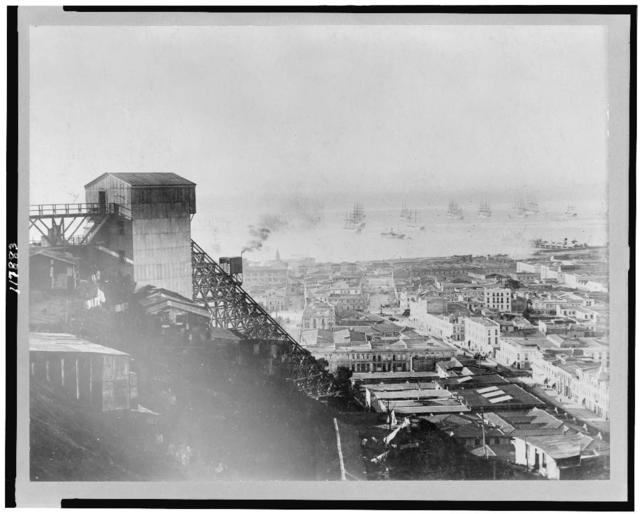 [Aerial view of Valparaíso, Chile, with cable railway on slope in foreground, and ships on water in background]
