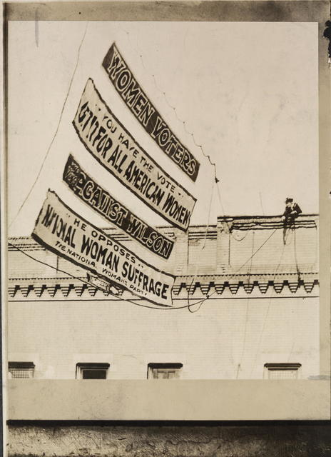 Campaign in Illinois. One of the big Woman's Party street banners being swung into place in Chicago by Miss Virginia Arnold, of Washington, national executive secretary of the Congressional Union for Woman Suffrage.  Democratic protest led to the removal of several of the banners after the necessary permission of owners of buildings had been secured and the street signs hung.