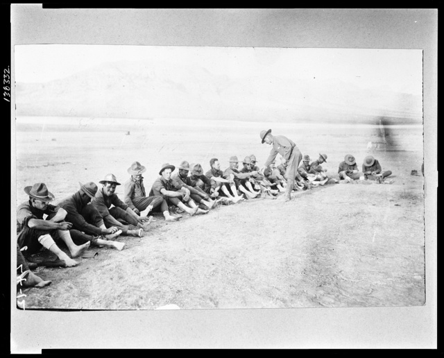 Capt. Napier inspecting feet of soldiers after days hike near San Antonio. Mexican-U.S. campaign after Villa