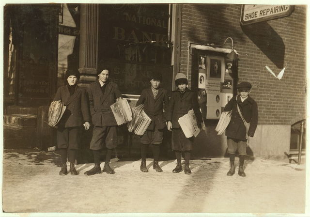 Group of newsies (youngest 10 years) selling Boston papers at noon. In Barre and Montpelier newsies are excused from school a little early at noon and at night in order to get to their papers earlier.  Location: Barre, Vermont / Lewis W. Hine.