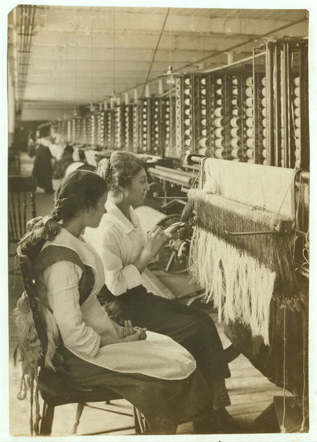 King Philip Mill. Drawer-in - Young learner - 14 years old, Yvette Frappier, and teacher who has been a drawer-in 9 years. Only girl in department has been learning a few weeks. Drawing thread through an eye in the harness.  Location: Fall River, Massachusetts / Lewis W. Hine.