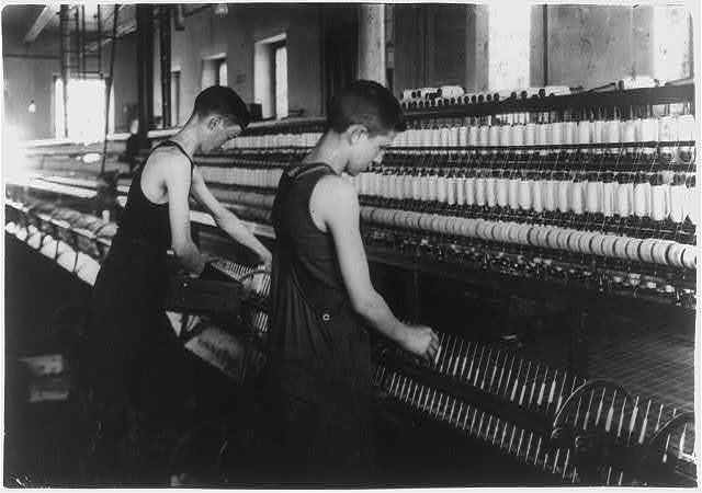 King Philip - Mule Spinning Room. Thomas Nicholls, 54 Kilburn St. Tube boy on the right - doffer on the left. Tube boy 14 years, doffer 16 years. Tube boy slips onto spindle holders. Location: Fall River, Massachusetts. / Lewis W. Hine.