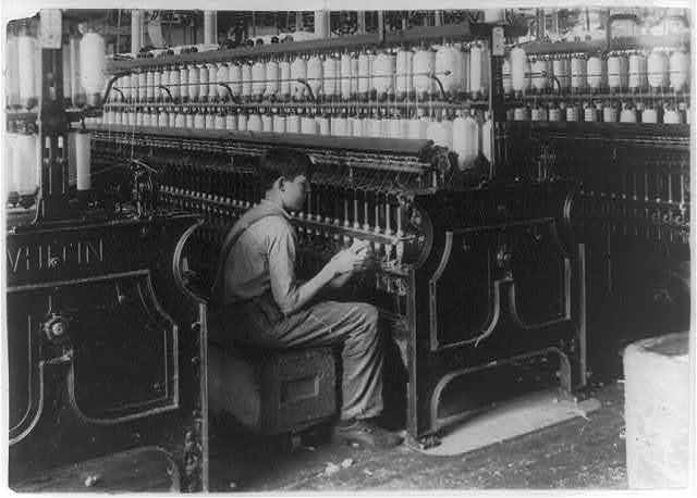 King Philip Spinning room. Oiler Boy - Oils all the spindles in this room. George Courtemonds, 114 Kellogg St. October 3, 1915, 14 years old.  Location: Fall River, Massachusetts / Lewis W. Hine.