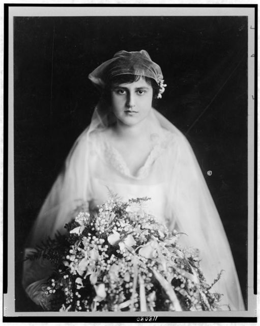 [Mrs. Henry Morgenthau, née Elinor Fatman, half-length portrait, facing front, in bridal gown, holding large bouquet]
