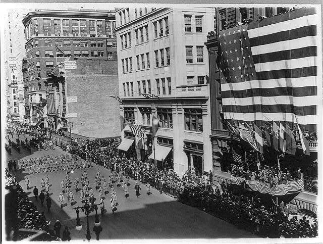 [News photos of N.Y. National Guard units preparing for active duty on Mexican border, May-Nov. 1916: Departure of 7th Regiment, parading down 5th Avenue, passing gigantic U.S. flag]