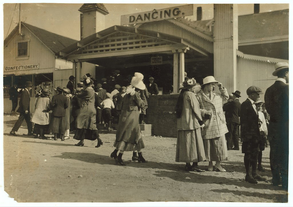 Sandy Beach. Two girls in foreground about 15. Mr. Tebbutt says dance hall bad conditions. Saturday evening dancing would be about the same as this. Penny picture machine attracting crowds. See 4184.  Location: Fall River, Massachusetts / Lewis W. Hine.