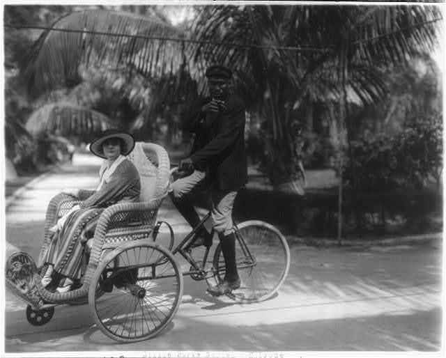 """[Stills of Billie Burke starring in motion picture, """"Gloria's Romance"""", 1916: being driven in bicycle sedan chair (108)]"""