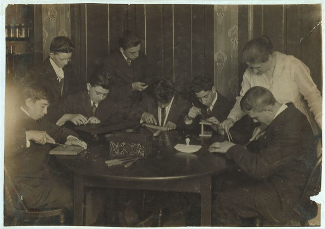 Wood carving group of working boys at King Philip Settlement - Names beginning at our right: 6. Frederick Reinhadt, 15, 147 Grant Street. 5. Arthur Bourque, 14, 415 Kilburn St., 3. Anthony Bello, 16, 75 Mt. Hope Ave. 8th grade Slade School - wants good education more than work. 1. Wm. Berupe, 15, 36 Assonet St., Sweeper, Iron Works, 7:30-11:30, 1-5. Barber Shop 7 years old, now Fridays and Saturday afternoons and until 12 at night. 4. Herman Reinhadt, 17, Hub Clothing Co. clerk. Was a doffer in the mule room. 7. Manuel Ferreira, 15, 27 Whittier St. Sweeper, Iron Works, same schedule as Berupe. 2. John Megna, 16, 75 Mt. Hope Avenue, Sweeper, Iron Works, - Two previous positions.  Location: Fall River, Massachusetts / Lewis W. Hine.