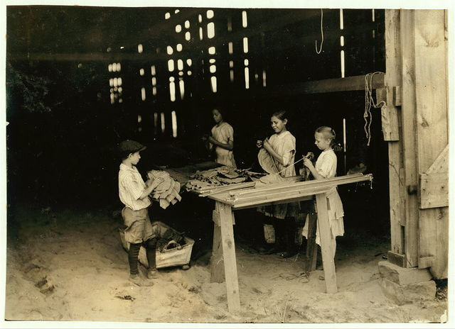 "10 year old leaf boy and three ""stringers,"" 10, 12, and 13 yrs. old. Tobacco shed of American Sumatra Tob. Co. In these two sheds were 41 girls and boys from 10 to 15 yrs., and only 24 girls and women of 16 and over. The leaf-boys get $1.50 a day and some of the stringers of 10 and 12 make $1.20 a day, according to the Supt.  Location: S[outh] Windsor, Connecticut / L.W. Hine."