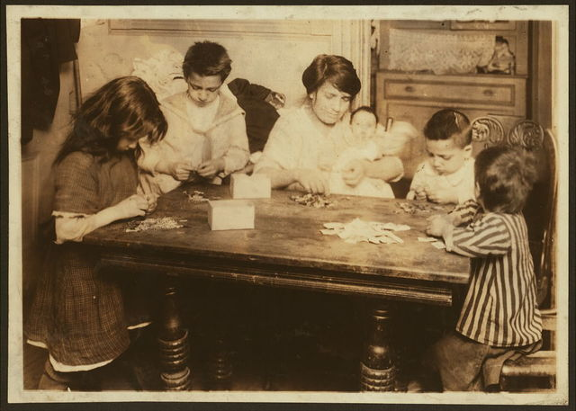 """Civarro family, 2106 Second Avenue, second floor back, working on patriotic flag pins. They get 3 cents a gross for inserting pin and putting onto card. Mrs. Civarro with her three-months-old baby in her arms is working with four children aged 10, 9, 7 and 5, and a younger child that does not work (2 years). They work irregularly (as Mrs. Civarro does the janitor work for the building which is in fair condition, and receives in return only the rent free of three small rooms), and their net income for this work is $2 a week. 8 members of the family sleep in one small inner room. The tenement is not licensed for homework. Baby was a premature child and very small and frail. """"It is so skinny."""" Husband is a laborer.  Location: New York, New York (State) / Lewis W. Hine."""