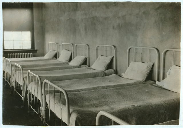 Crowded dormitory (one wall) in Training School for Deaf Mutes. See Gibbons report.  Location: Sulphur, Oklahoma / Lewis W. Hine.