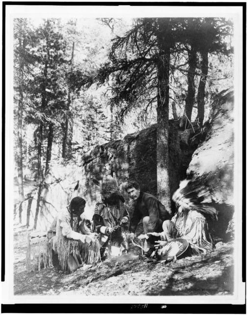 [Ernest Thompson Seton, with three Blackfeet Indians, demonstrating how to start a fire using a bow and a stick, rocks and trees in background]