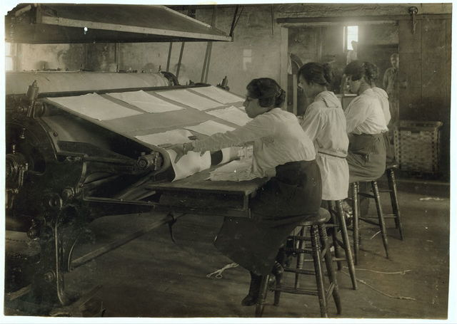 Girls working at mangle in Bonanno Laundry, 12 Foster Wharf. All are 15 years old and go to continuation school.  Location: Boston, Massachusetts / Lewis W. Hine.
