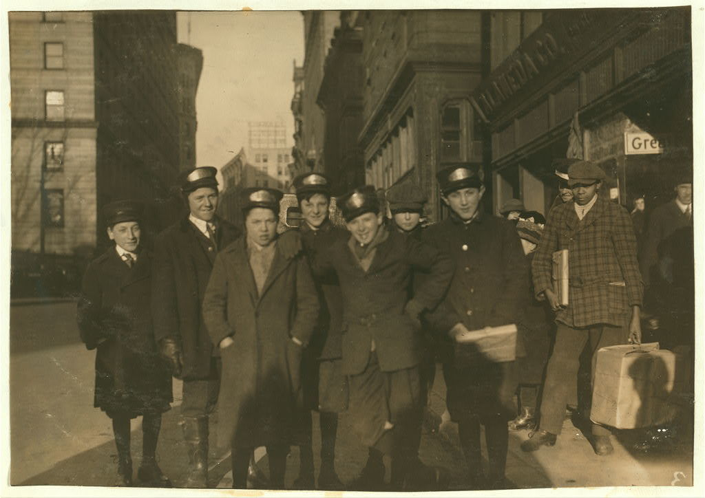 Group of messengers, mostly Metropolitan Messenger and Mailing Co., on Tremont Street at 3:15 p.m. Some of the sweller [i.e., smaller?] ones are: Timothy Sexton,325 Columbia Street, Cambridge. Harry S. Friedman, 93 Brighton Street, Boston. Joseph Selva, 6 Fourth Street, East Cambridge. George O. Mara, 10 Leyland Street. Smallest one is: Soll Hamber, 71 Madison Avenue, Everett. He is Messenger #18 for Special Delivery Messenger Co., 3 Somerset Street.  Location: Boston, Massachusetts / Lewis W. Hine.