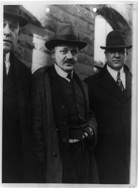 [Hans Schwartz, three-quarter length portrait, standing, facing slightly right, with two detectives on way to court, New Jersey]
