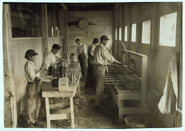 """[Interior of workshop of Sanitary Ice Cream Cone Co. See 4830. Boys packing cones are John Myers, 14 years old and a boy 12 years old who is working steady now. Boss said: """"He said he wasn't going to school so I took him."""" See 4830.]  Location: [Oklahoma City, Oklahoma] / [Lewis W. Hine]"""