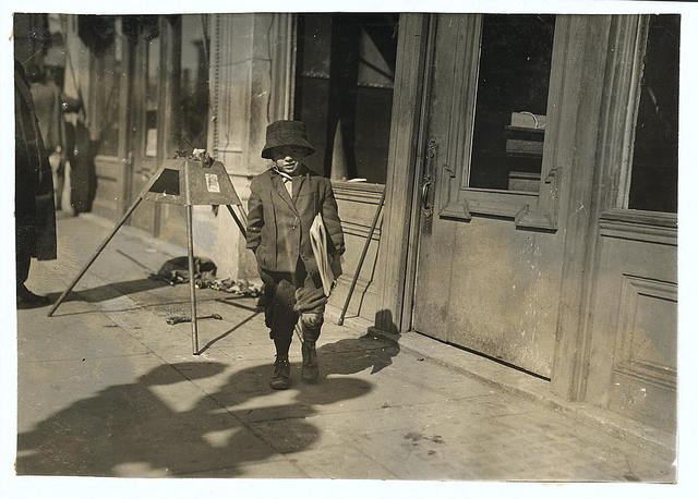 """John Dowers, 7 years old, lives at 108 W. Frisco St. Starts out at 5 a.m. some days. Father is blind and sells newspapers. John is a pretty good beggar. Was seen trying to borrow a dollar from the bank to """"get father a watch"""" (father is blind).  Location: Oklahoma City, Oklahoma / Lewis W. Hine."""