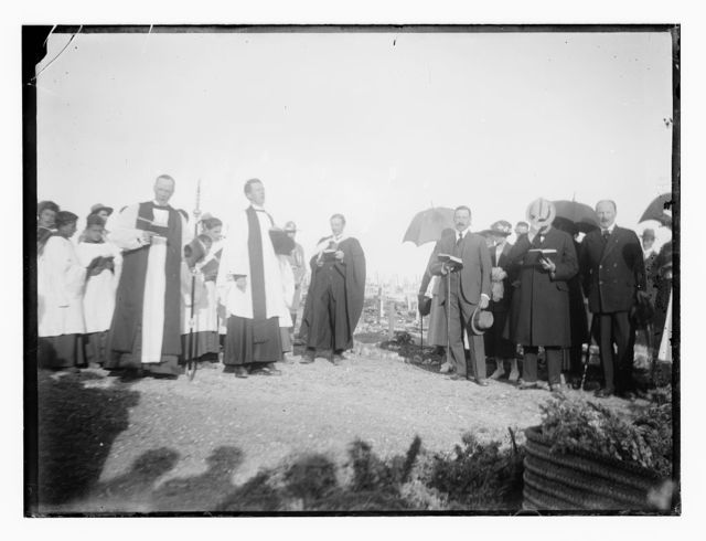 [Men and women, including possibly Winston Churchill and Herbert Samuel, with Christian clergy in a military cemetery]