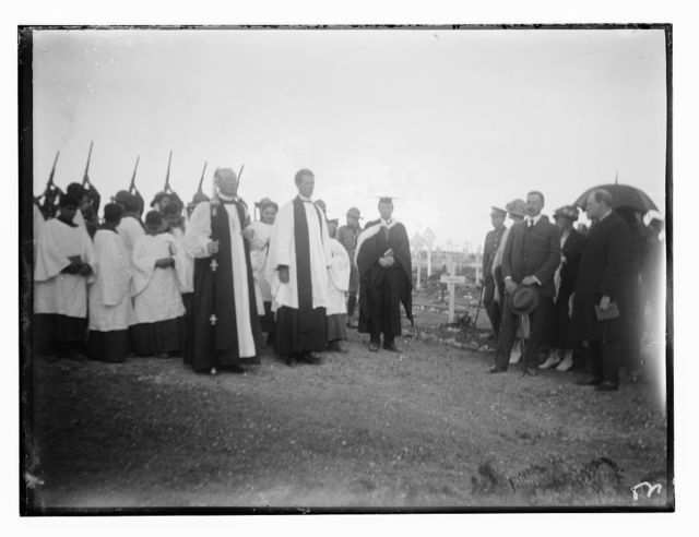 [Men and women, possibly Winston Churchill and Herbert Samuel, with Christian clergy in a military cemetery]