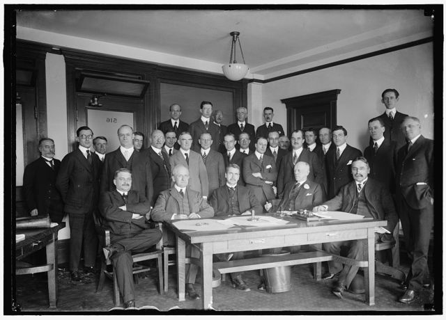 NAT. ADVISORY COMM. FOR AERONAUTICS. MEETING OF EXEC. COMMITTEE WITH THE AIRCRAFT MANUFACTURERS ASSN., HELD IN MUNSEY BLDG. SEATED: DR. S.W. STRATTON; DR. JOS. S. AMES; ADMIRAL D.W. TAYLOR; DR. CHAS. D. WOLCOTT, CHAIRMAN; DR. M.I. PUFIN. STANDING ON FLOOR: DR. W. CHRISTMAS; 5 UNIDENTIFIED; SIDNEY D. WALDON; CHAS. F.