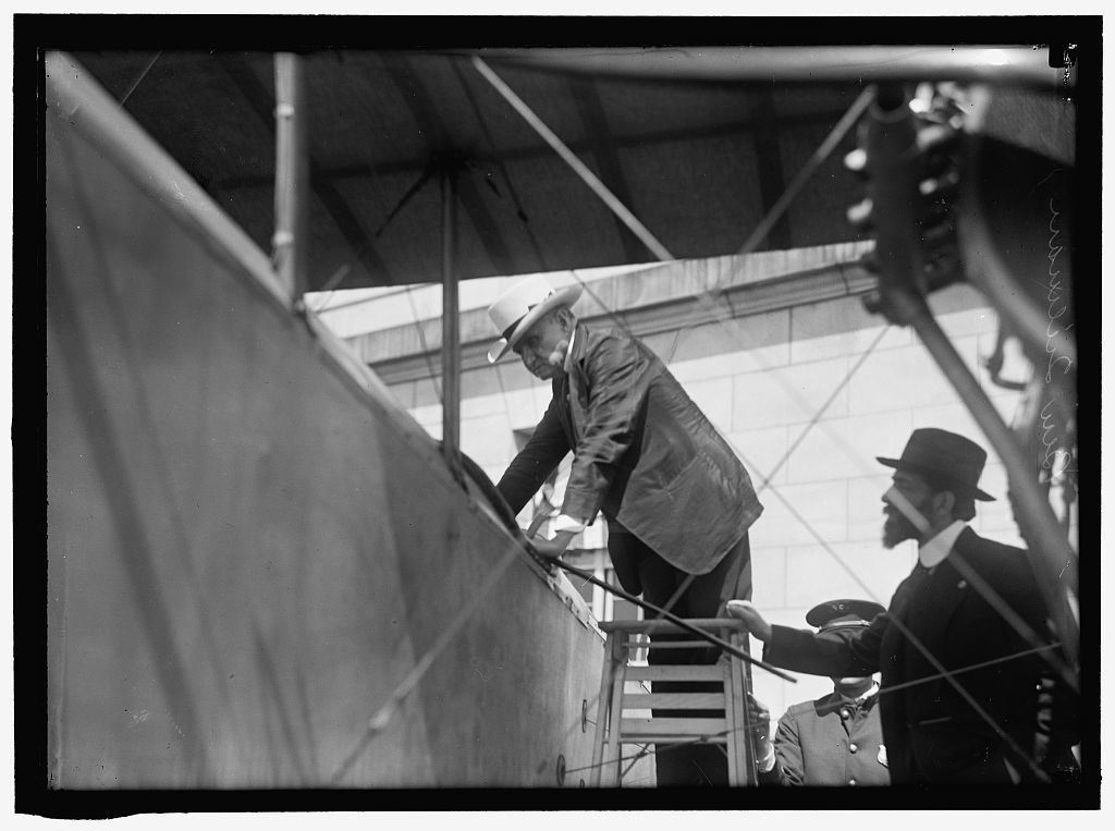 NATIONAL AERO COAST PATROL COMMN. CURTISS BIPLANE 2 ENGINES, WITH FLOATS, EXHIBITED AT S.O.B. SEN. BEN TILLMAN CLIMBING INTO PLANE; AUGUSTUS POST AT RIGHT