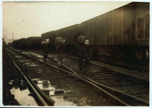 Stealing coal from railroad coal-yard.  Location: Boston, Massachusetts / Lewis W. Hine.