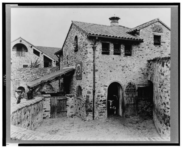 """[""""Surprise Valley Farm,"""" Arthur Curtiss James property, Beacon Hill Road, Newport, Rhode Island. Courtyard with bull in doorway]"""