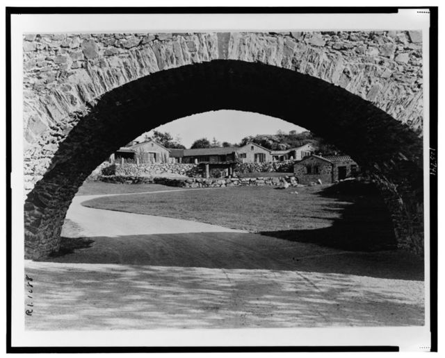 """[""""Surprise Valley Farm,"""" Arthur Curtiss James property, Beacon Hill Road, Newport, Rhode Island. Stone cottages through archway]"""