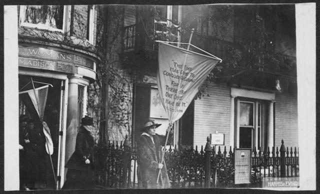 """The day after the police announce that future pickets would be given limit of 6 mos. in prison, Alice Paul led picket line with banner reading """"The time has come to conquer or submit for there is but one choice - we have made it."""" She is followed by Mrs. Lawrence Lewis [Dora Lewis].  This group received 6 mos. in prison."""