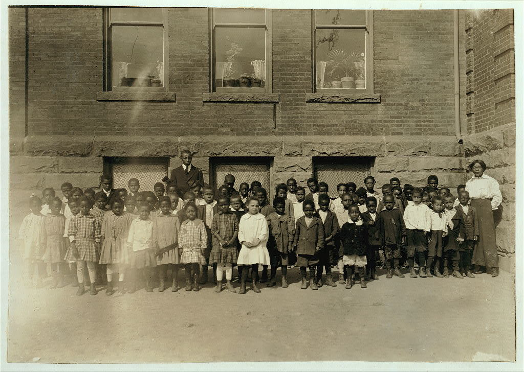 """The lone teacher in charge of a room where 123 Kindergarten and First Grade children are enrolled. Dunbar School. Teacher said: """"There are only 70 here to-day. There must be an epidemic around."""" Principal in background. See Bliss report.  Location: Muskogee, Oklahoma / Lewis W. Hine."""