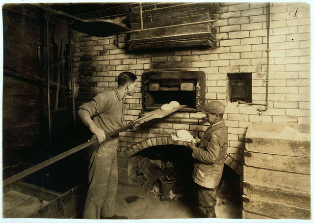 [Vincenzo Messina, 15 years old and brother Angelo, 11 years old, baking bread for father, 174 Salem Street. Vincenzo is working nights now, from 5 P.M. to 5 P.M. Usually works on day shift. Angelo helps a great deal, tends store and helps bake too.]  Location: [Cambridge, Massachusetts] / [Lewis W. Hine]