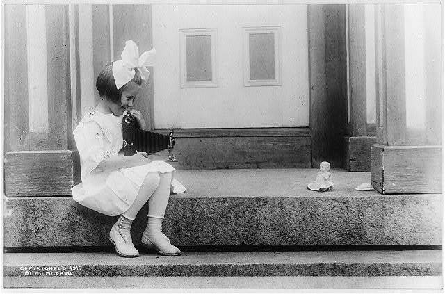 Young girl taking a Kodak picture of her doll