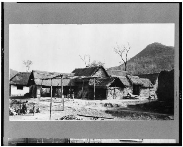 [China--mud-brick houses with thatch roofs, people in yard in foreground]