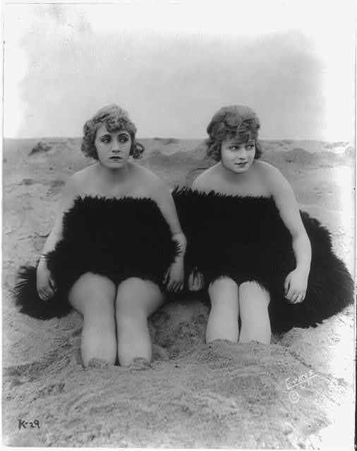 Claire Anderson and Rose Carter [seated on beach, draped in a fur, with feet in sand]