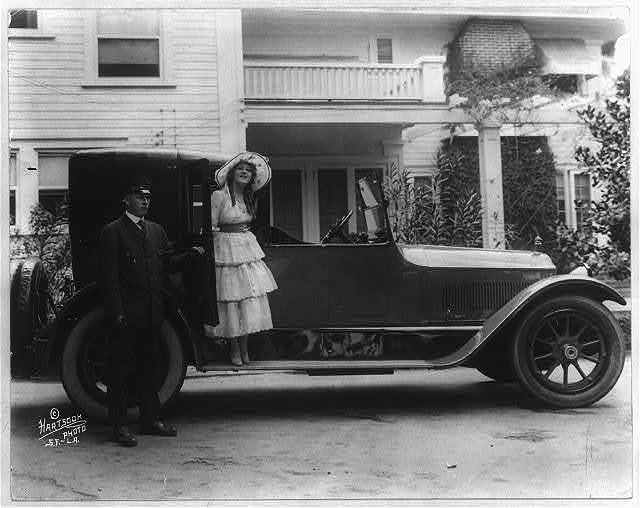 Mary Pickford standing on the running board of an automobile, as chauffeur holds door open